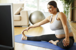 Beautiful pregnant woman exercising by watching television